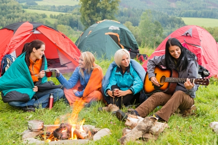 women friends: Girls on vacation camping with tents listening girl playing guitar