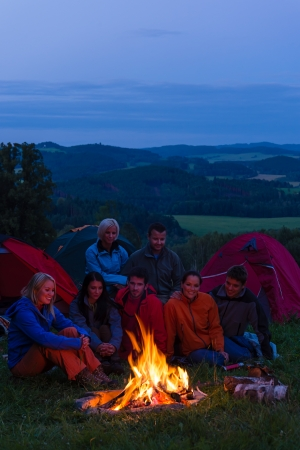 Friends watching fire together beside camp and tents in dark photo