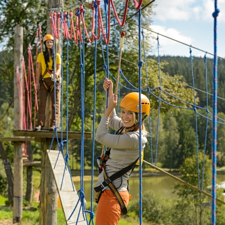 lipno: Smiling woman having fun in adventure park rope ladder Stock Photo