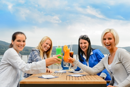 Cheerful women toasting with cocktails at outdoor restaurant summer terrace photo