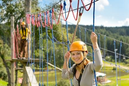 Femme dans le casque d'escalade sur une échelle de corde dans le parc adrénaline