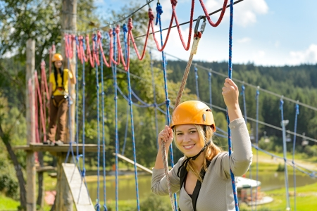 Woman in helmet climbing on rope ladder in adrenalin park Stock Photo