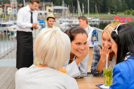 Women gossiping about men sitting at harbor bar summer terrace photo