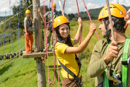 adventure sports: Visitors in adventure park clambering with ropes wear protective helmets