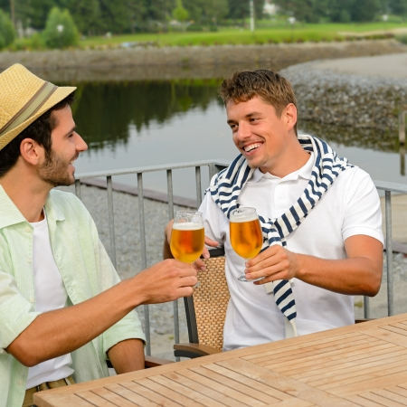 manhood: Cheerful male friends drinking beer at sidewalk pub restaurant terrace Stock Photo