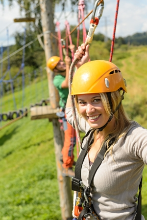 adventure sports: Smiling woman climbing on high wire in adventure park