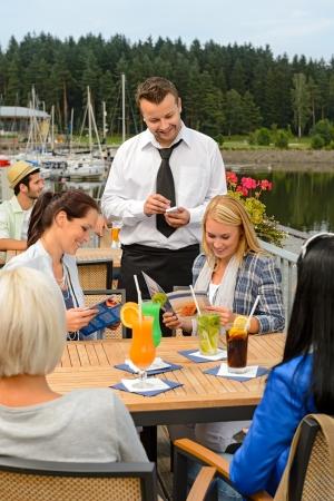 tomando refresco: Camarero tomando pedidos en el bar de la acera de las mujeres jóvenes Foto de archivo