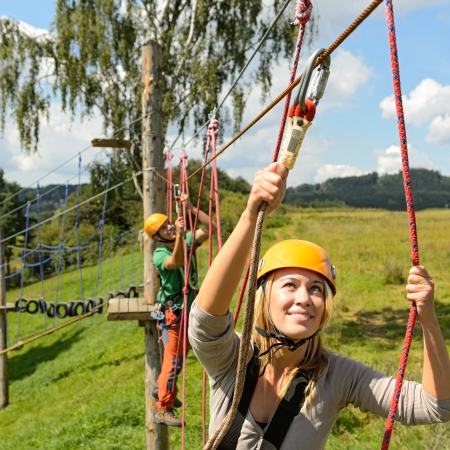 rope bridge: Young woman climbing in adventure park with friend summer freetime