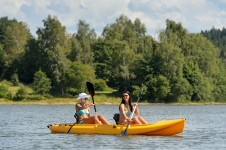 lipno: Young women in bikinis kayaking on river summertime Stock Photo