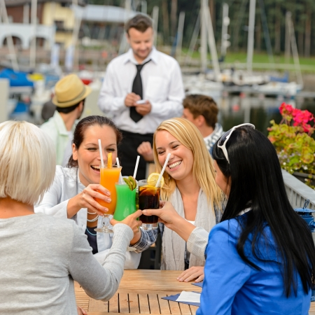 Women celebrating with cocktails at harbor restaurant photo