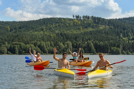Young kayaking friends having fun in scenic view summer holiday photo