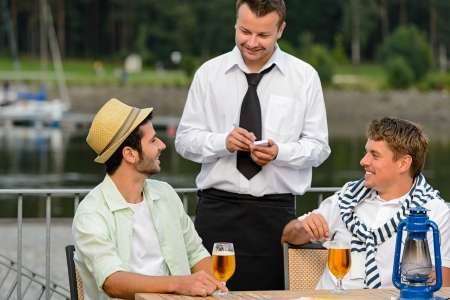 lipno: Smiling waiter taking order from men customers outdoor bar