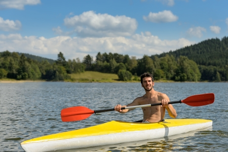 lipno: Young sportsman kayaking on sunny day on lake
