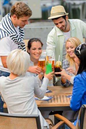 Group of cheerful young people toasting with cocktails outdoor terrace Standard-Bild