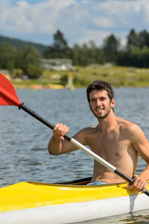Young muscular sportsman kayaking in the sunshine photo