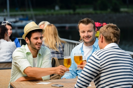 Three male friends relax drinking beer night out restaurant terrace Stock Photo