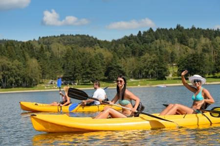 Friends enjoying summertime kayaking on river holiday freetime Standard-Bild