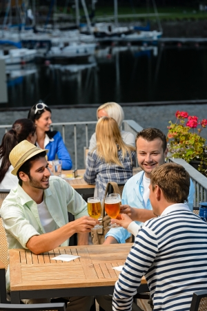 Three men drinking beer at terrace bar enjoying night out photo