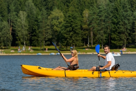 lipno: Young couple on summer weekend kayaking on pond