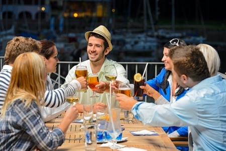 clinking: Grupo de amigos jovenes que tintinean sus copas celebrando la noche de fiesta