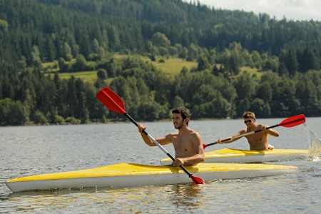 Young men kayaking summertime vacation on river paddling photo