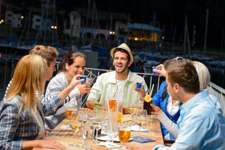 Young people drinking shots at outside bar night out Stock Photo