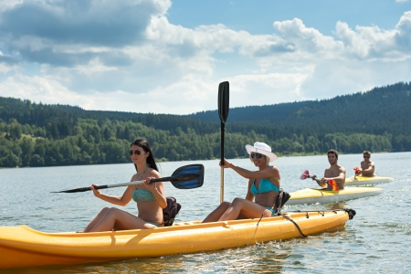 paddling: Young women rowing on kayaks with friends summertime