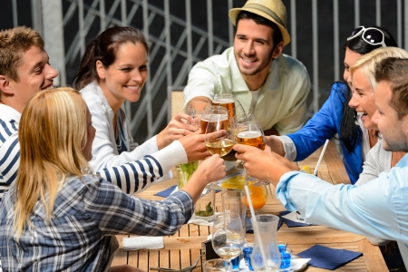 friends at bar: Group of cheerful young people toasting with drinks night out Stock Photo