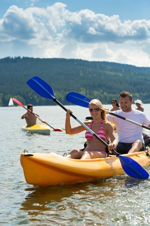 lipno: Young friends kayaking in summertime on lake holiday