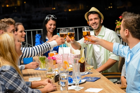 Group of young friends drinking beer outdoors terrace night out photo