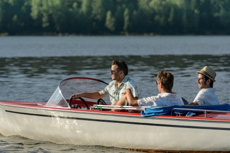recreational vehicle: Young men driving speed boat enjoying sunshine