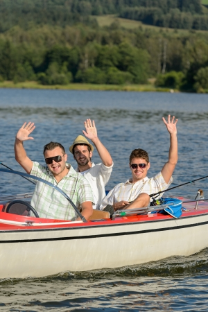 Cheerful young men sitting in motorboat enjoying sunshine Stock Photo - 18867756
