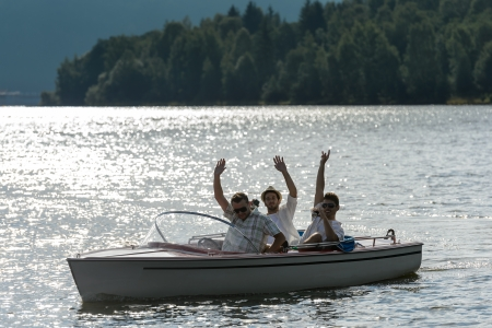 speed boat: Silhouette of waving young men sitting in motorboat