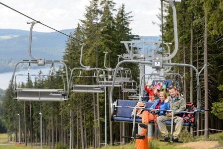 Waving young people sitting on chairlift going through forest Stock Photo - 18881877