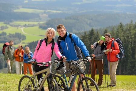 lipno: Sporty cyclist couple and hikers posing during springtime weekend