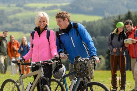 Cheerful cyclist couple with mountain bikes relaxing countryside photo