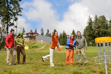 Group of friends throwing frisbee disc to basket in park Standard-Bild