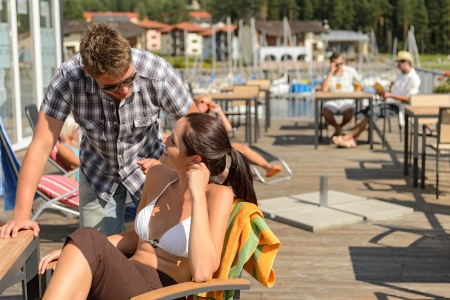 beach bar: Young couple talking at bar beside beach summer terrace Stock Photo