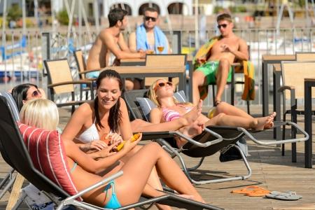 Chatting girls lying on deckchair sunbathing in bikinis sunny day Stock Photo - 18881181