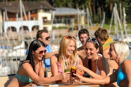 Beautiful women in bikinis toasting with cocktails at beach Stock Photo - 18881845