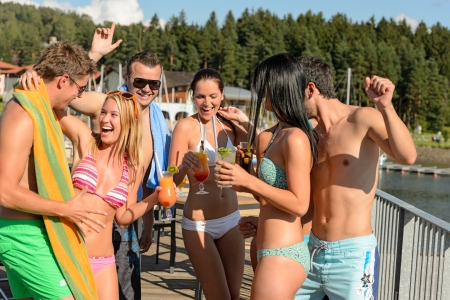 Young people having party at beach drinking cocktails
