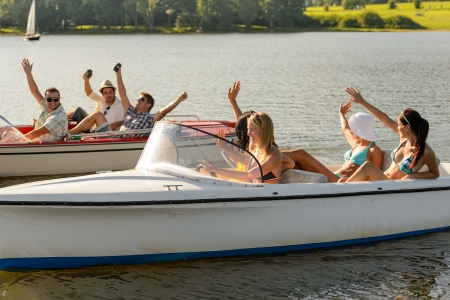 Waving young friends sitting in motorboats enjoying summertime Stock Photo - 18867760