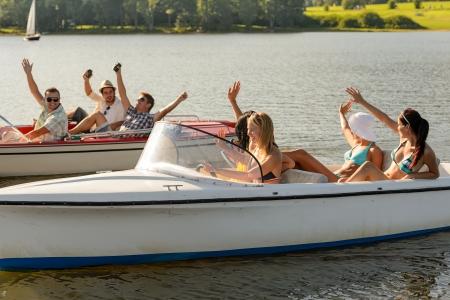 lipno: Waving young friends sitting in motorboats enjoying summertime