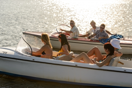 Group of women and men navigating motorboats summer lake photo