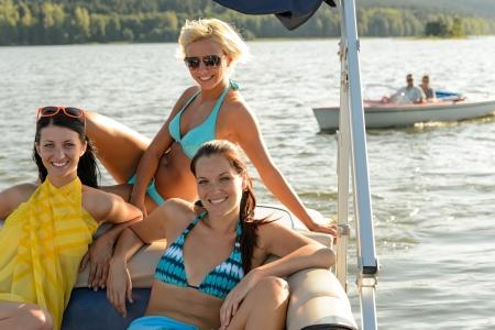 Young women sunbathing on boat sailing on lake Stock Photo - 18867914