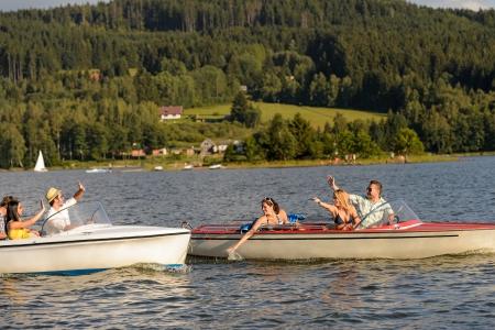 lipno: Young friends having fun in motorboats waving and splashing water Stock Photo