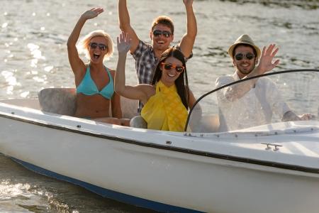 the boat on the river: Saludar con la mano a los j�venes en gafas de sol sentado en verano motora