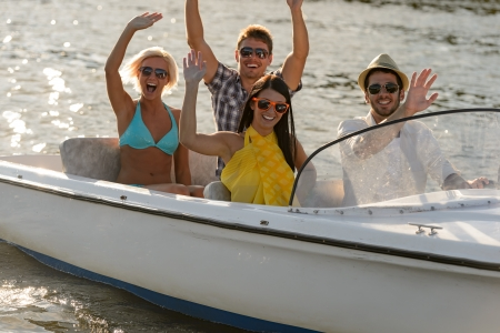boating: Waving young people in sunglasses sitting in motorboat summertime Stock Photo