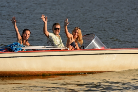 Young people waving from motorboat enjoying summer break Stock Photo - 18867766