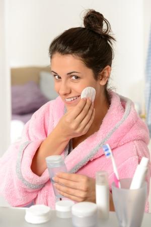 productos de belleza: Mujer joven sonriente limpiar la cara con un algodón